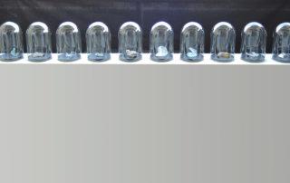 GLÄSERNE ZEUGEN, geschmolzene Glasscherben unter Glashauben, 200 x 20 cm auf 80 cm hohem Sockel